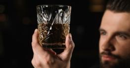 Mann bestellt Whisky an der Bar.