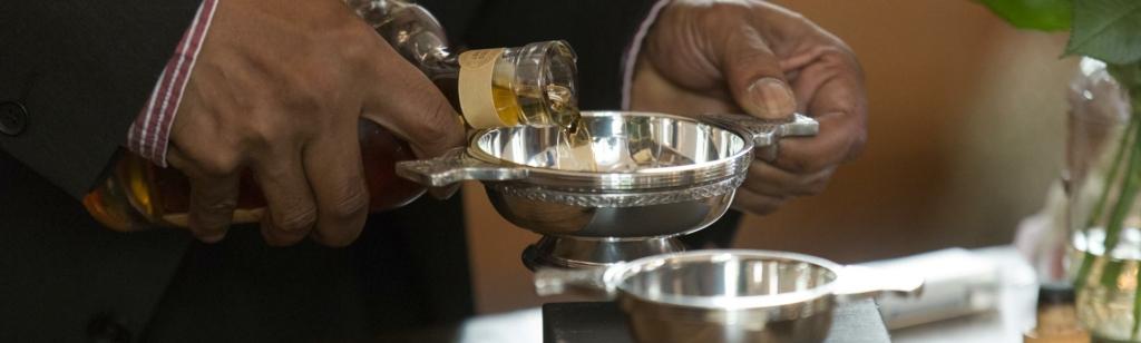 Mann portioniert Whisky-in schottischem Quaich für Zeremonie.