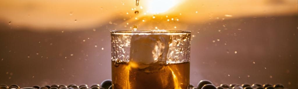 Whisky on the rocks bei Sonnenuntergang im Sommer.
